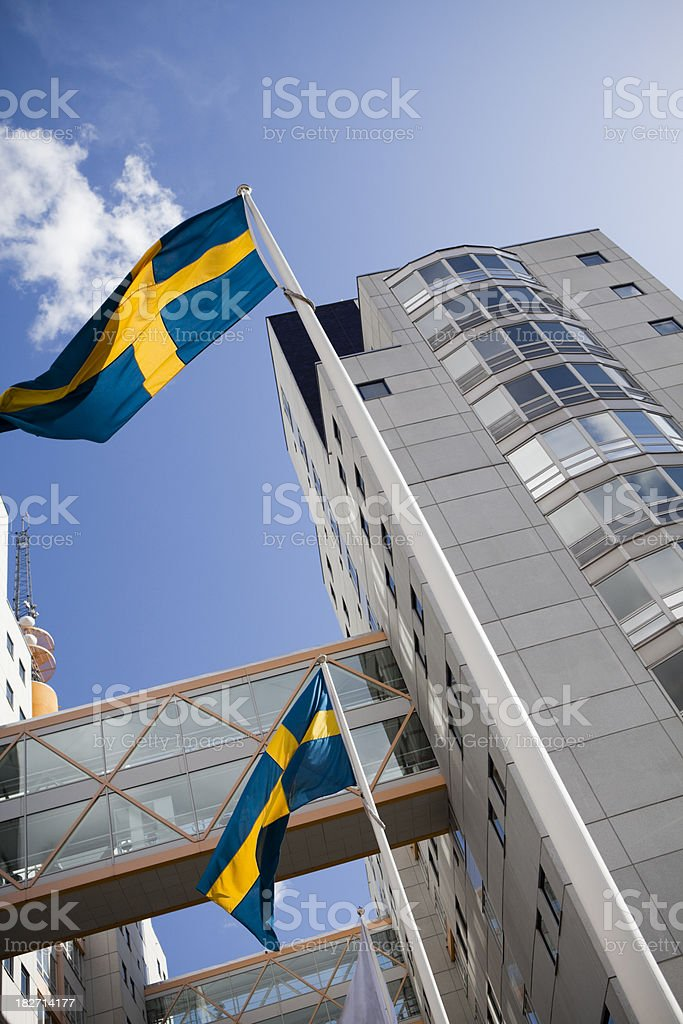 Swedish flag in front of corporate office buildings stock photo