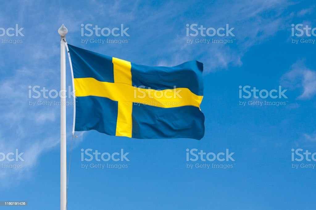 Swedish flag Close-up on a Swedish flag waving atop of its flagpole. Close-up Stock Photo