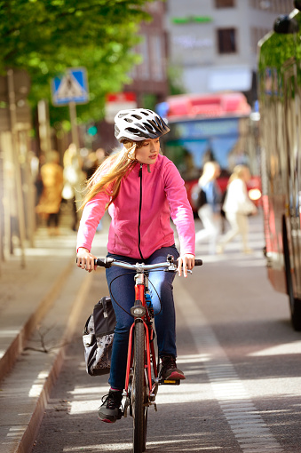 Girl and bicycle, traffic in background