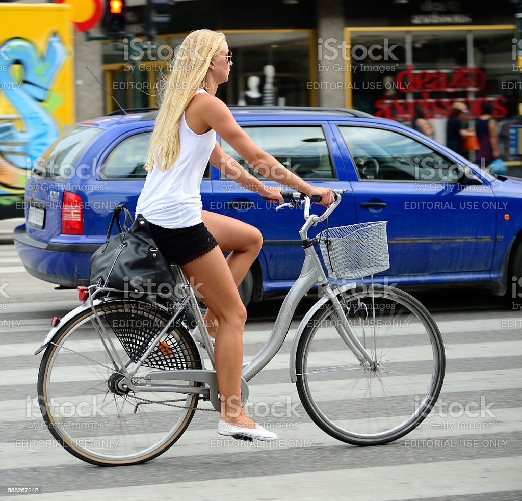 Swedish girl in summer clothes on bicycle in city traffic stock photo