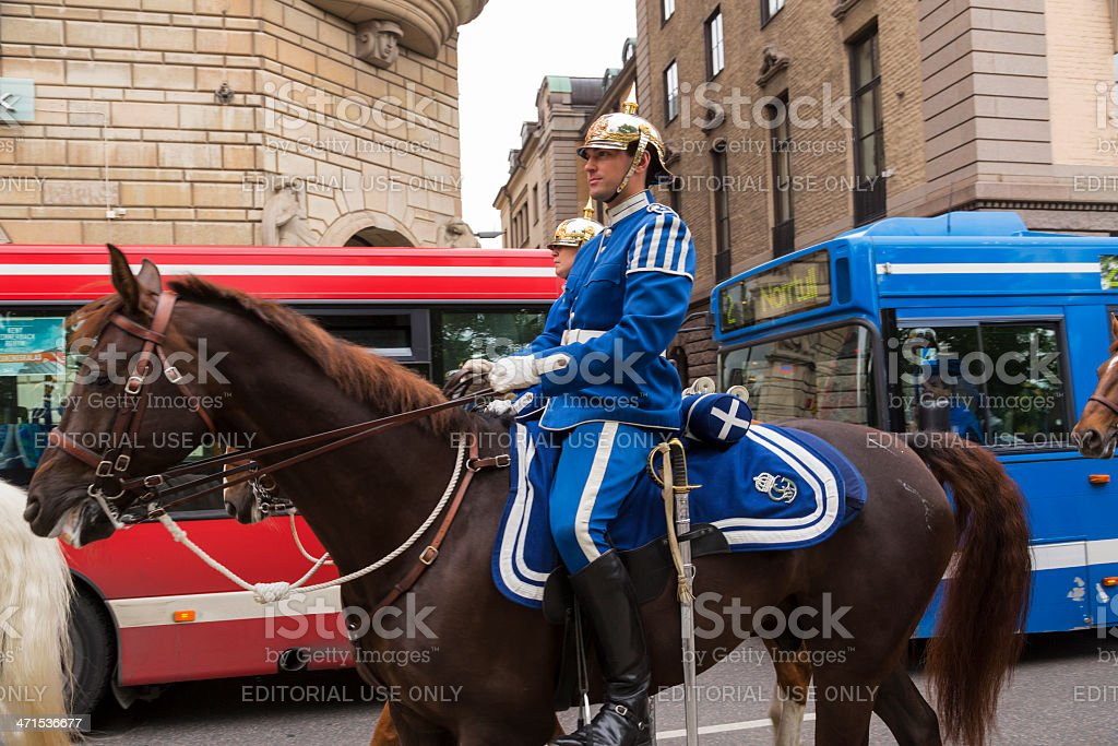 Swedish Mounted Guard passing a buses in Stockholm royalty-free stock photo