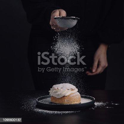 Swedish semla typical wheat bun with cream Photo taken in studio, woman spreading powder sugar on fresh semla Studio shot, dark low key photo