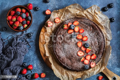 Swedish traditional chocolate cake Kladdkaka with fresh berries, strawberries and blueberries. On a blue background, seen from above flat lay perspective.