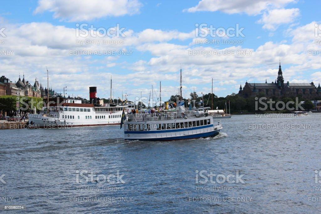 Svenska vintage passagerarfartyg med en skorsten. Retro ship turistattraktion för en sightseeing på bakgrunden av gamla stan hamnen med museum och byggnader - Royaltyfri Blå Bildbanksbilder