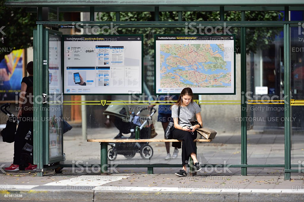 Swedish young woman at bus stop, using mobile smart phone stock photo