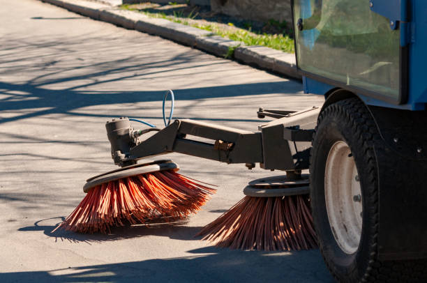 sweeper in the process of cleaning the sidewalk. sweeper in the process of cleaning the sidewalk. street cleaning equipment street sweeper stock pictures, royalty-free photos & images