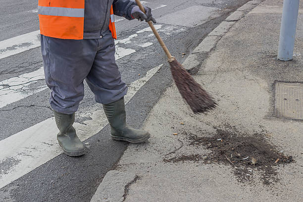sweeping and pushing a broom 2 Road sweeper sweeping and pushing a broom. Cleaning walkway with broom made Of twigs. street sweeper stock pictures, royalty-free photos & images