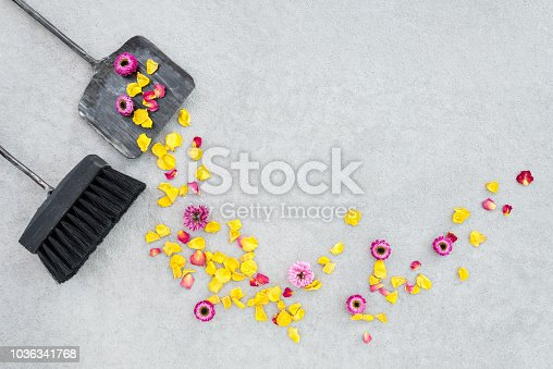 istock Sweeping away dry flowers and rose petals in the garden patio 1036341768