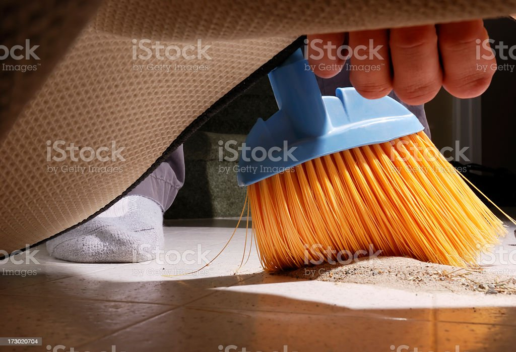 Sweeping Dirt Under the Carpet. stock photo