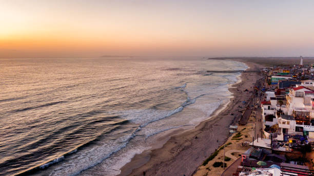 Sweeping Drone Point Of View Of The Beach And Boardwalk Near The International Border Wall In Playas Tijuana, Mexico Aerial drone view of the Boardwalk, beach with palapas and umbrellas and the border wall between Tijuana, Mexico, and the United States frontier field stock pictures, royalty-free photos & images