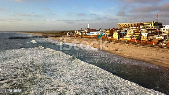 Aerial drone view of the Boardwalk, beach with palapas and umbrellas and the border wall between Tijuana, Mexico, and the United States