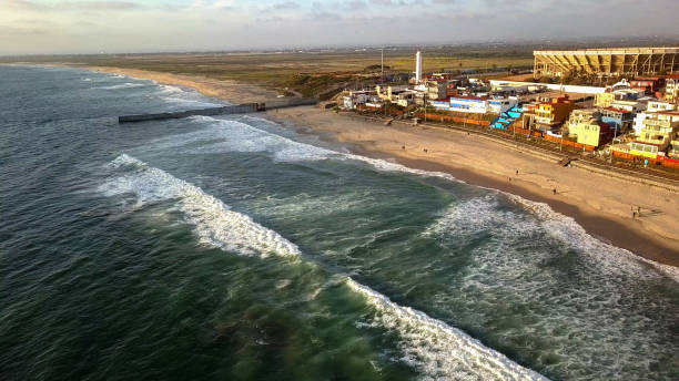 Sweeping Drone Point Of View Of The Beach And Boardwalk Near The International Border Wall In Playas Tijuana, Mexico Aerial drone view of the Boardwalk, beach and the border wall between Tijuana, Mexico and the United States frontier field stock pictures, royalty-free photos & images