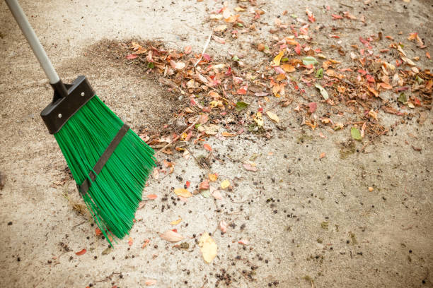 Sweeping dry leaves with broom.Autumn, fall season.Sweep the leaves, sweep people, clean the garden.Maintenance worker in park garden cleans the roads with plastic garden broom .Copy space stock photo