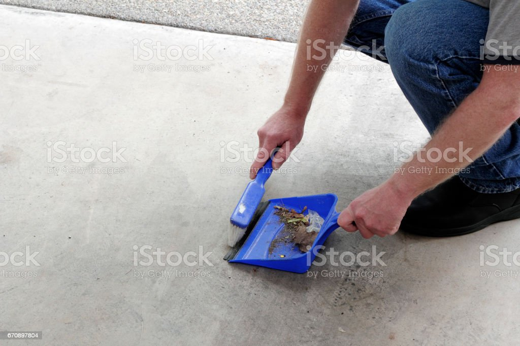 Sweeping Floor Dirt into a Dustpan stock photo