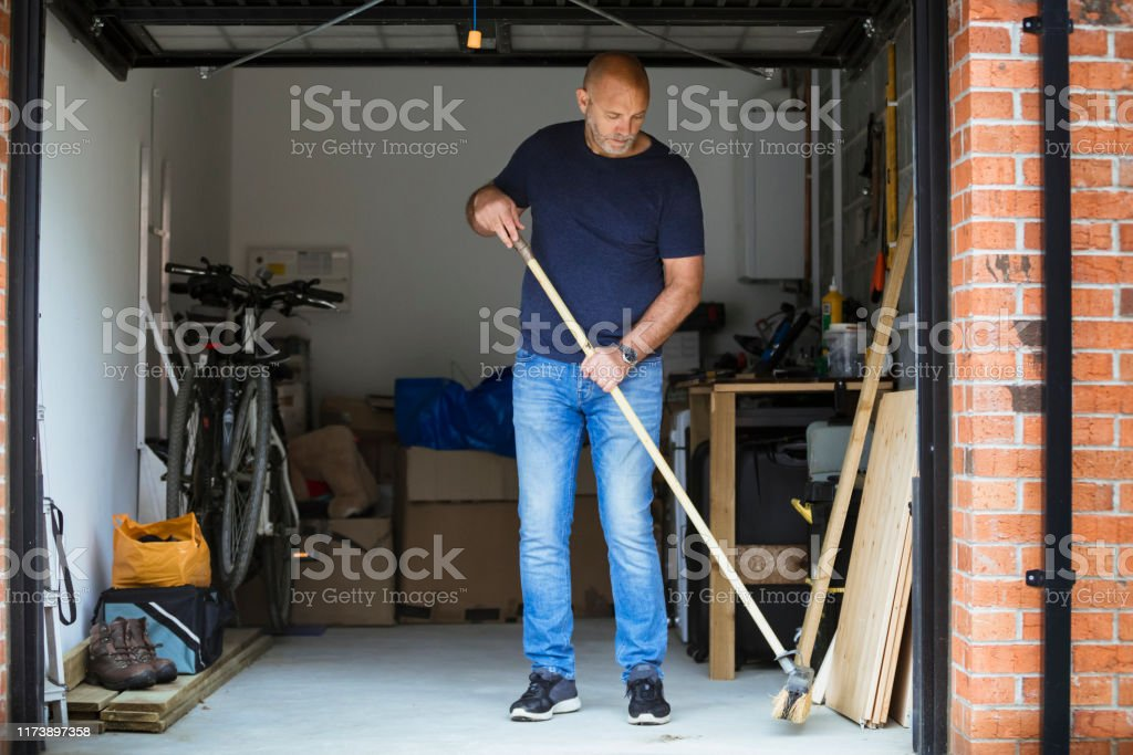 Sweeping His Garage Floor A man is sweeping the floor up his home garage with a large brush. The garage door is open. 40-49 Years Stock Photo