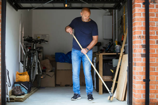 Sweeping His Garage Floor A man is sweeping the floor up his home garage with a large brush. The garage door is open. man cave stock pictures, royalty-free photos & images
