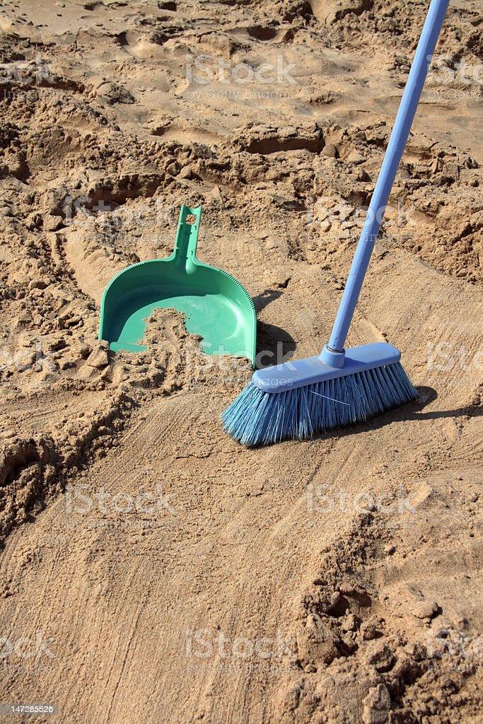 Sweeping the beach (irony) stock photo