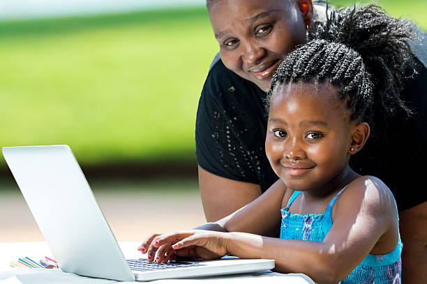 Sweet african girl and mother with laptop. stock photo