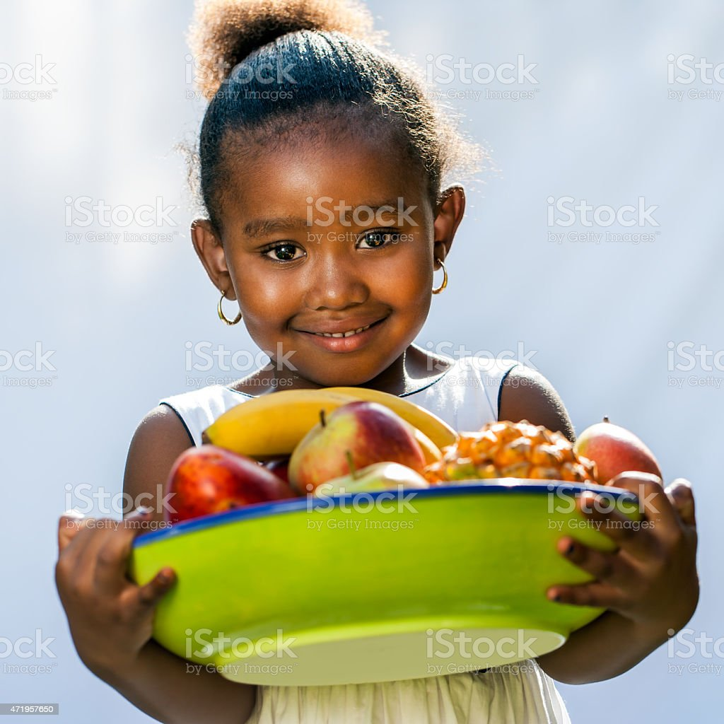 Sweet afro american girl with fruit bowl. stock photo