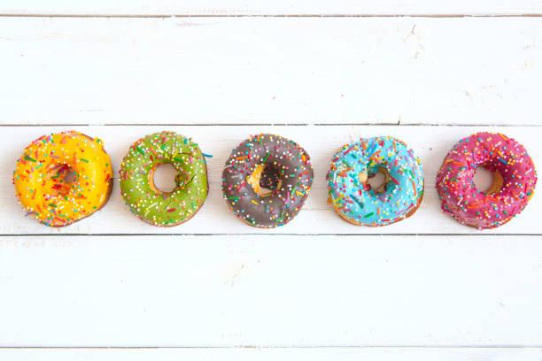 süße und bunte donuts auf weißer holztisch mit textfreiraum. ansicht von oben - hausgemachte gebackene donuts stock-fotos und bilder