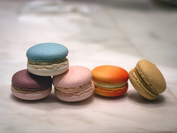Sweet and colorful French macarons on marble table at high tea time in pastry shop of cafe and coffee shop stock photo