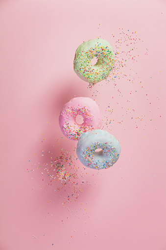istock Sweet and colourful doughnuts with sprinkles falling or flying in motion 930716276
