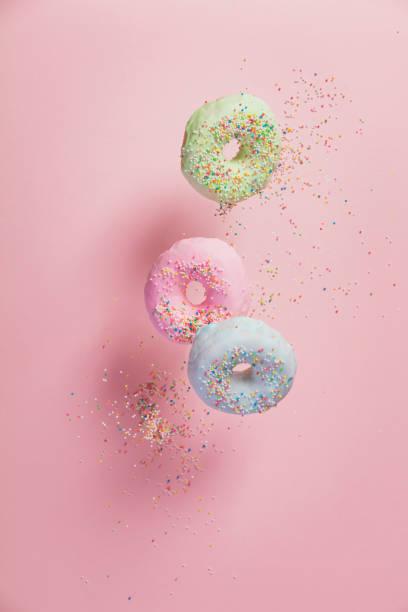 sweet and colourful doughnuts with sprinkles falling or flying in motion - posypka zdjęcia i obrazy z banku zdjęć