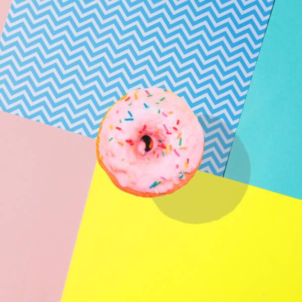 Süßer und köstlicher rosa Donut fliegt mit einem starken Schatten in die Luft. – Foto