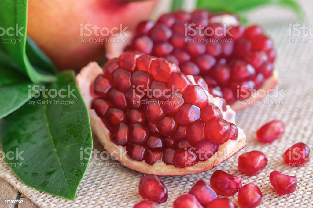 Sweet and juicy Indian red pomegranate on wood table in close up view copy space. Delicious fruit which have high vitamin c and antioxidant for good skin. Healthy concept for background or wallpaper. stock photo