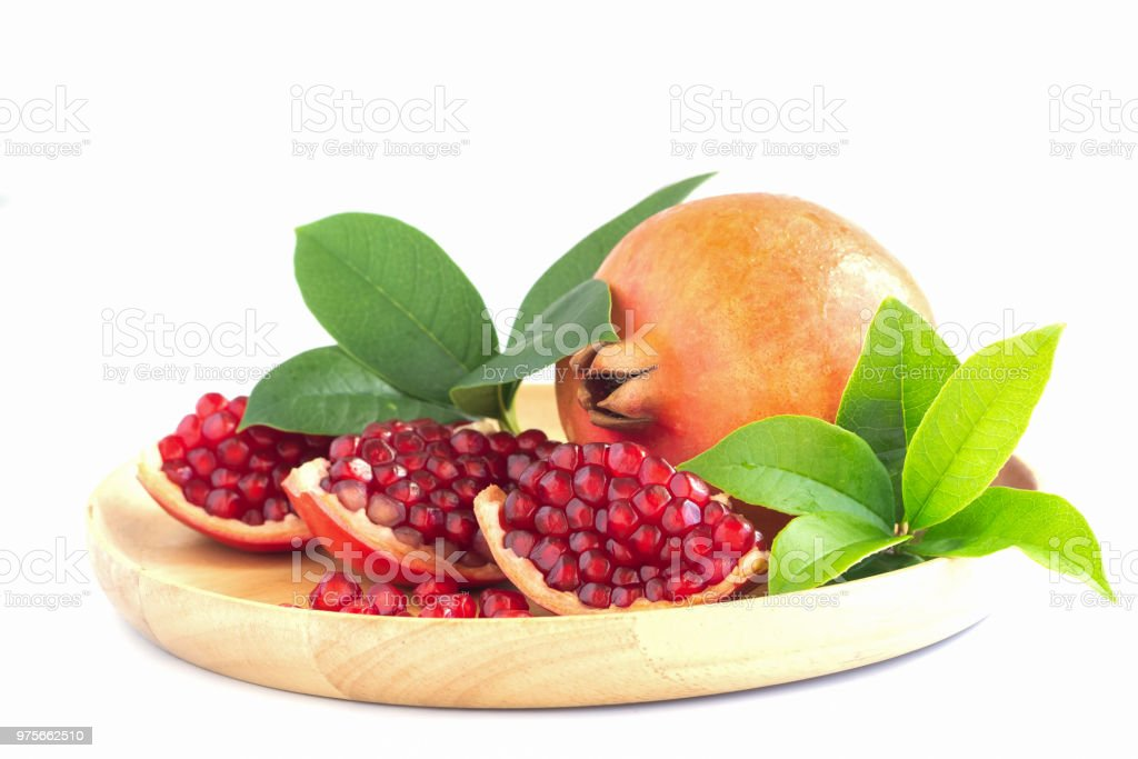Sweet and juicy Indian red pomegranate on wooden plate on white isolated background easy to use for design. Healthy and delicious fruit which have high vitamin c and antioxidant for good skin. stock photo