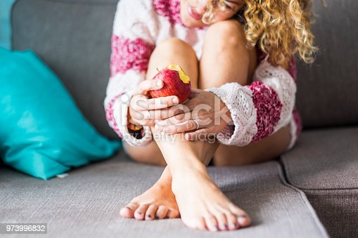 sweet and tender lonely caucasian lady at home sitting on the sofa eating a healthy red apple. hug herself to have care and protect. focus on the fresh fruit. smile and enjoy loneliness