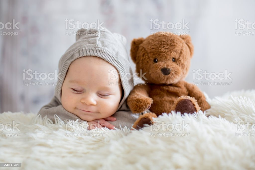 Sweet baby boy in bear overall, sleeping in bed with teddy bear stock photo