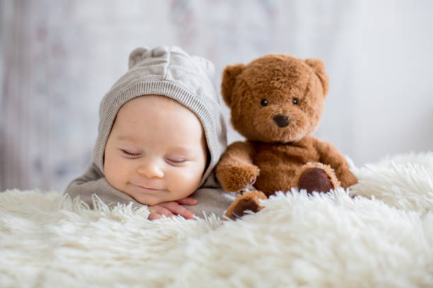 sweet baby boy in bear overall, sleeping in bed with teddy bear - new born baby zdjęcia i obrazy z banku zdjęć