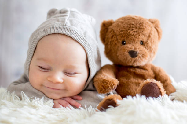 sweet baby boy in bear overall, sleeping in bed with teddy bear - innocence stock pictures, royalty-free photos & images