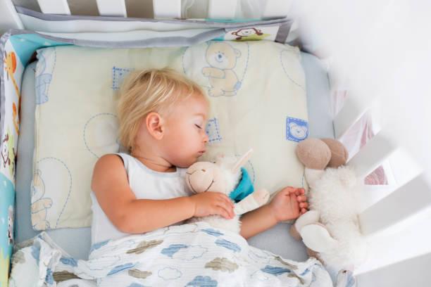 süße baby junge in lässigen kleidung, schlafen im bett mit teddybär stofftiere - jungendecken häkeln stock-fotos und bilder