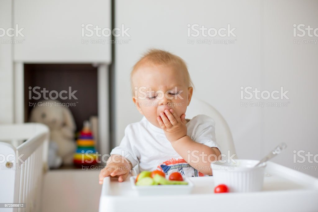 Sweet baby child, boy, eating mashed food and fresh vegetables, sitting in high baby chair stock photo