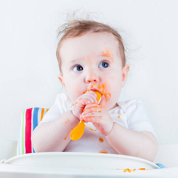 Sweet baby eating carrot stock photo