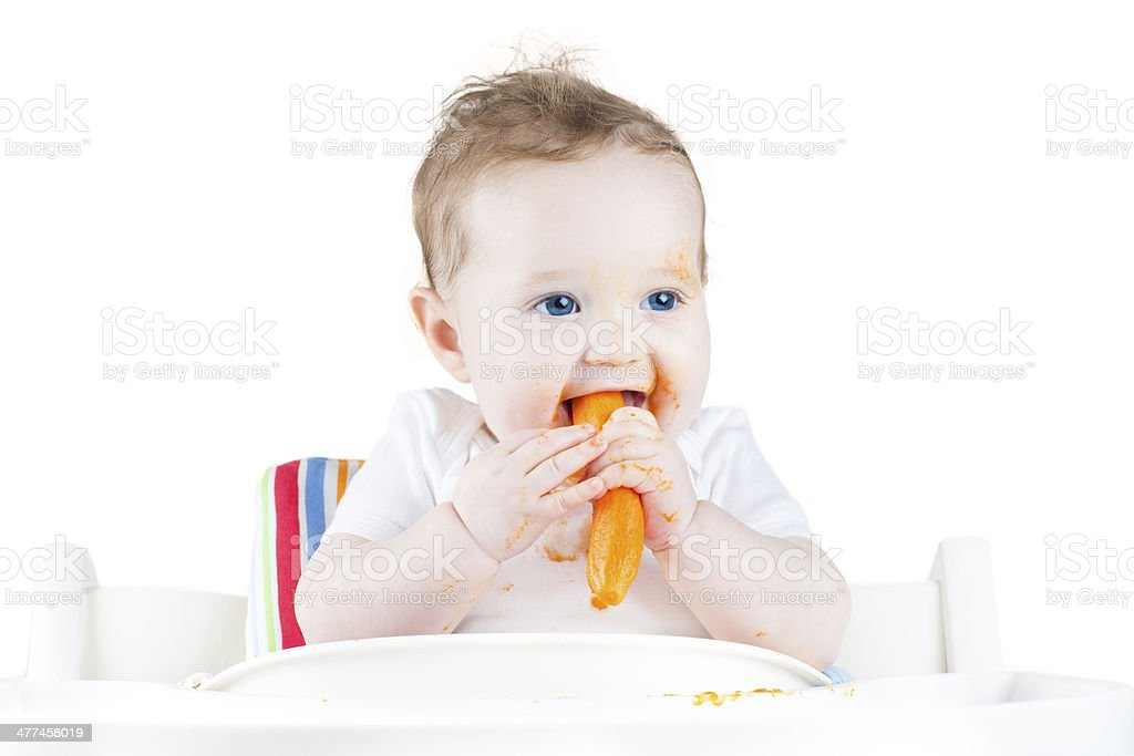 Sweet baby eating her first solid food in white chair stock photo