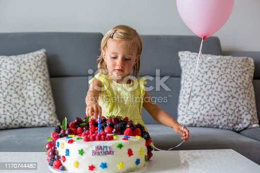 istock Sweet baby girl in cute yellow dress, celebrating her second birthday with homemade cake 1170744482