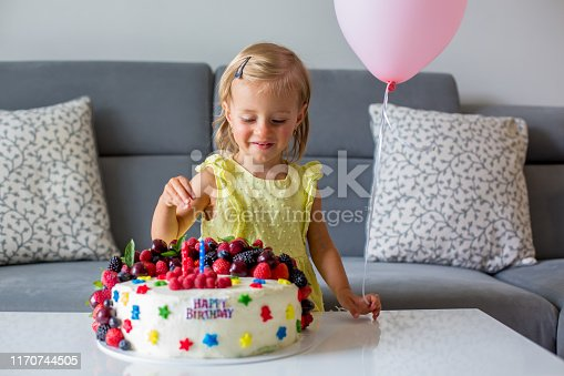 istock Sweet baby girl in cute yellow dress, celebrating her second birthday with homemade cake 1170744505