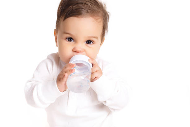 Sweet baby holding bottle and drinking water stock photo