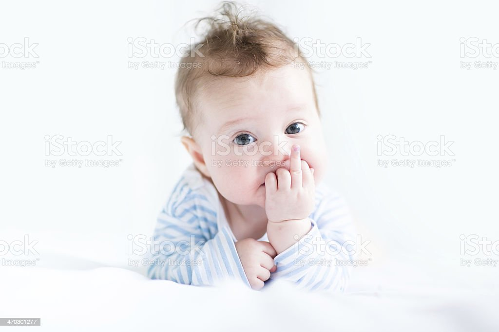 Sweet baby in a blue shirt sucking on its finger stock photo