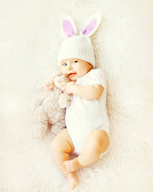 süße Baby Mütze mit Hasenohren und Teddybär Spielzeug auf dem Bett liegend – Foto