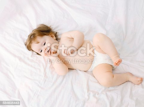 1084486306 istock photo Sweet baby lying on the bed at home, top view 534605443