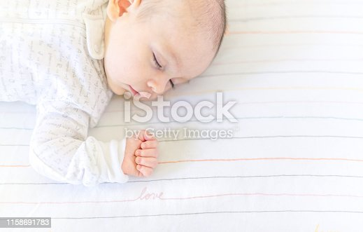 Darling 3 month old newborn baby sleeps in a peaceful neutral nursery, peaceful and quiet baby asleep and resting. The word Love