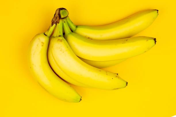 zoete bananen op de gele achtergrond. kopiëren van ruimte - kalium stockfoto's en -beelden