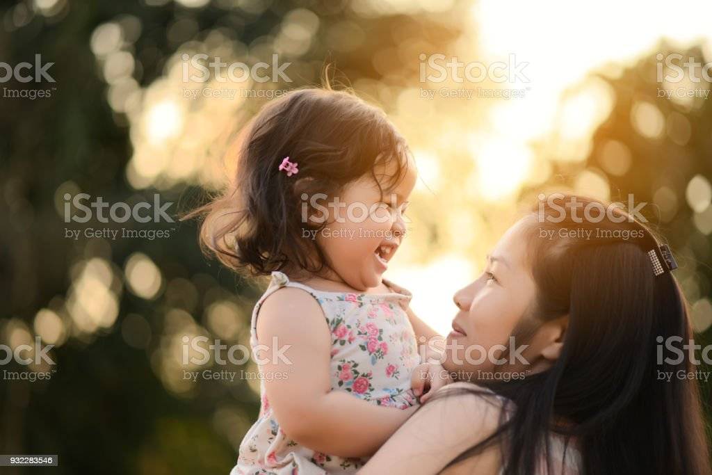 Sweet Beautiful baby girl with hug of mother and playing. Happy loving family kissing and hugging. stock photo