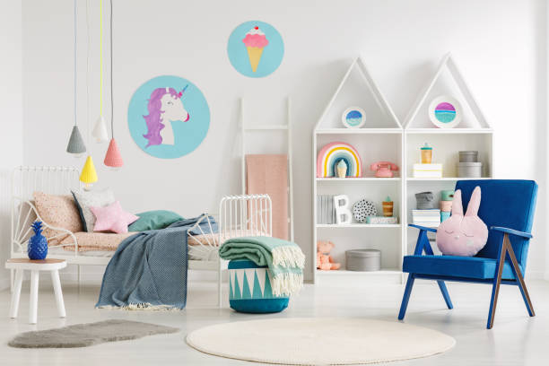 sweet bedroom interior for a kid with a blue armchair, rabbit pillow, bed, unicorn and ice cream posters and shelves - unicorn bed imagens e fotografias de stock