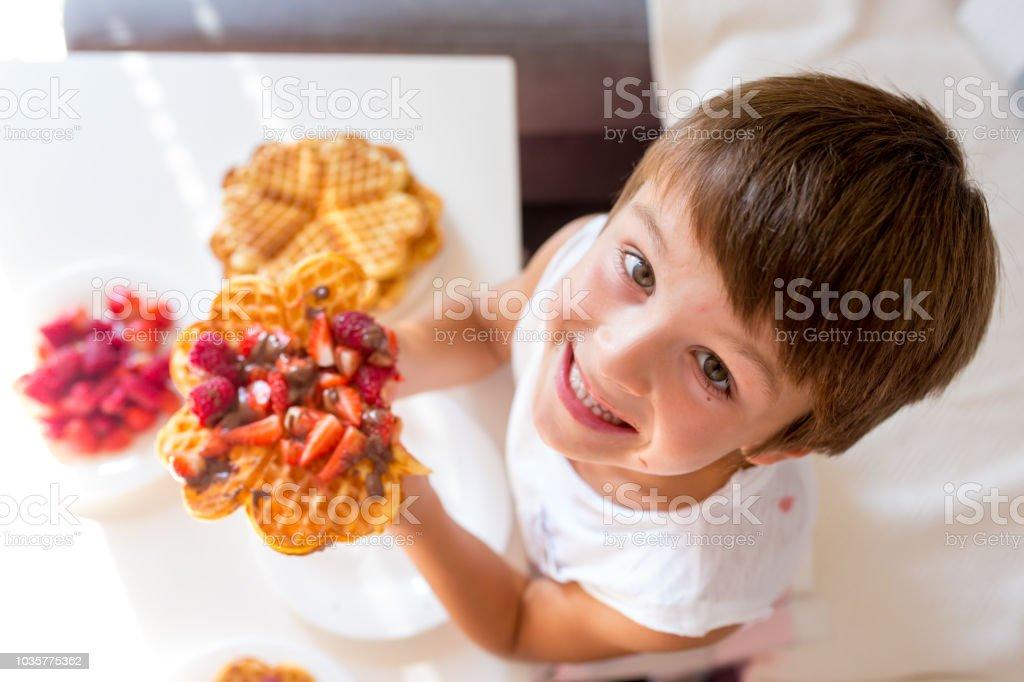 Garçon doux anniversaire, manger une gaufre belge avec fraises, framboises et chocolat - Photo