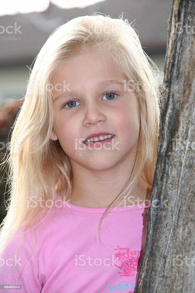 sweet blond little girl standing on a tree stock photo